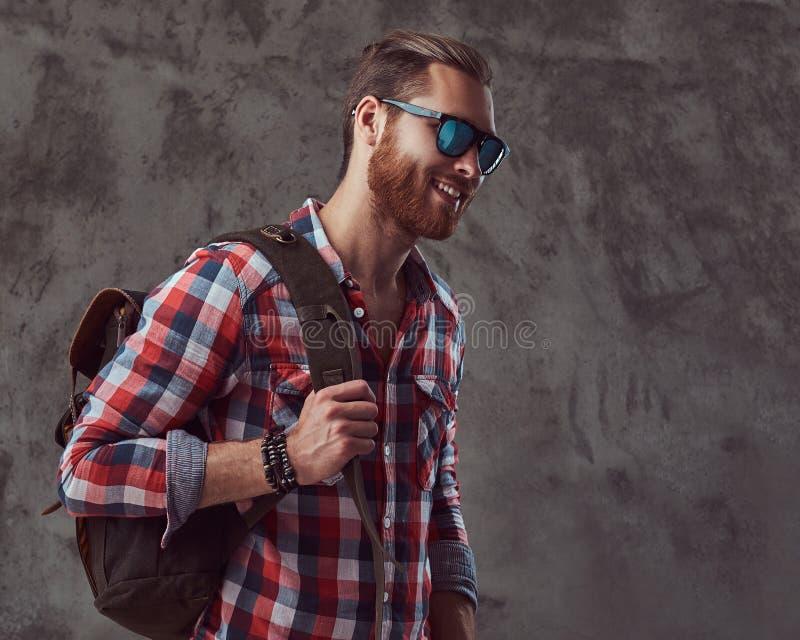 Hübscher stilvoller Rothaarigereisender in einem Flanellhemd und -Sonnenbrille mit einem Rucksack, werfend in einem Studio auf ei stockfoto