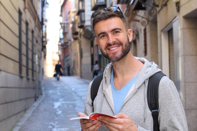 Hübscher Student, der auf dem Campus lächelt lizenzfreie stockfotos