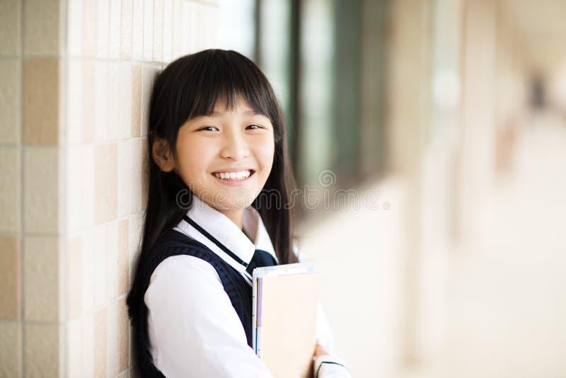 Hübscher Student, der Bücher vor Klassenzimmer hält stockbild