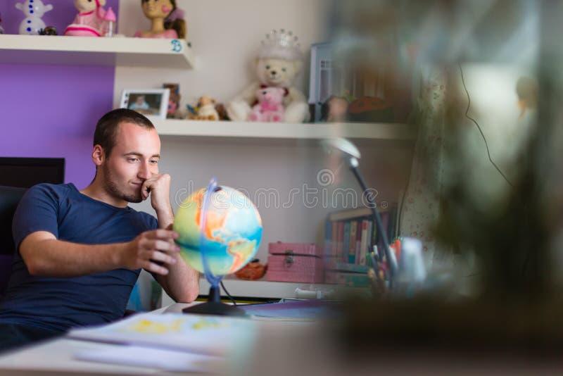 Hübscher Student, der unter Verwendung eines globus studing ist stockbild