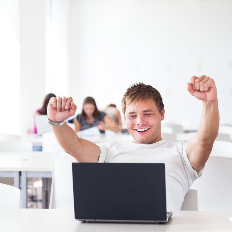 Hübscher Student mit Laptop-Computer in der Universitätsbibliothek stockbilder