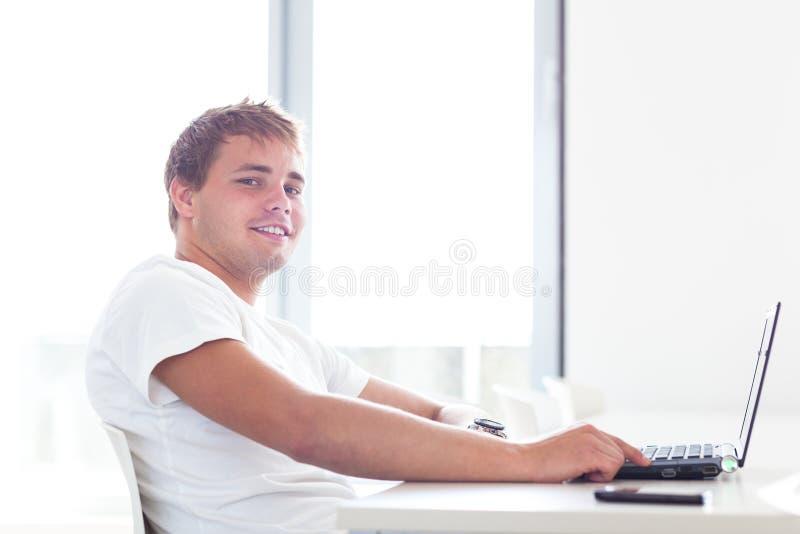Hübscher Student mit Laptop-Computer im Universitäts-libr lizenzfreies stockbild