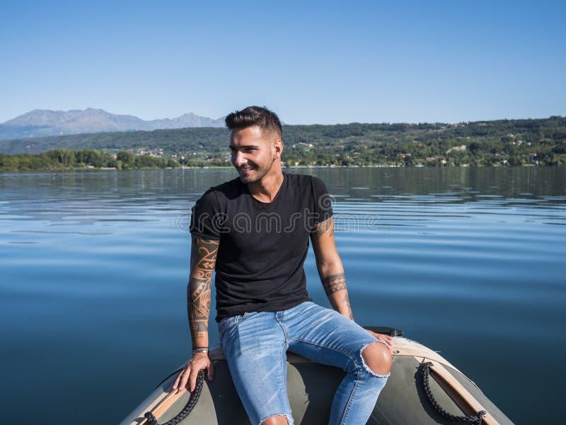 Hübscher tätowierter junger Mann im Boot lizenzfreie stockbilder