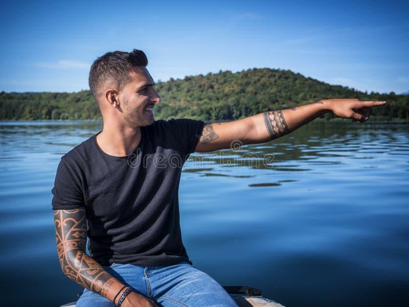Hübscher tätowierter junger Mann im Boot stockbild