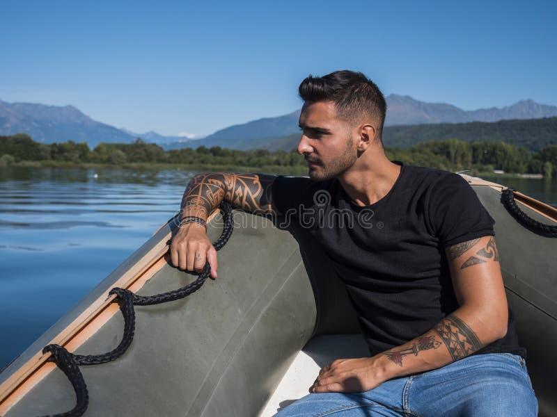 Hübscher tätowierter junger Mann im Boot stockbilder