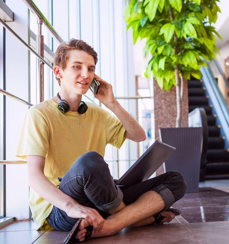 Hübscher Teenager, der telefonisch spricht stockbild
