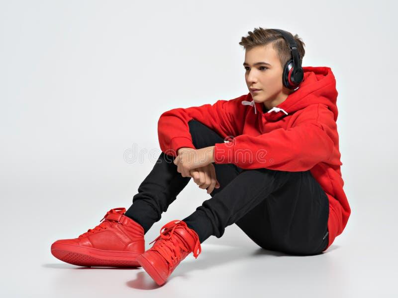 Hübscher Teenager mit den Kopfhörern obenliegend stockfoto