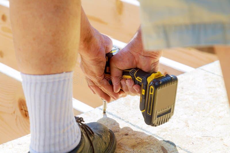 hübscher Tischler, der eine Terrasse des Holzfußbodens im Freien in Bau des neuen Hauses installiert stockfoto