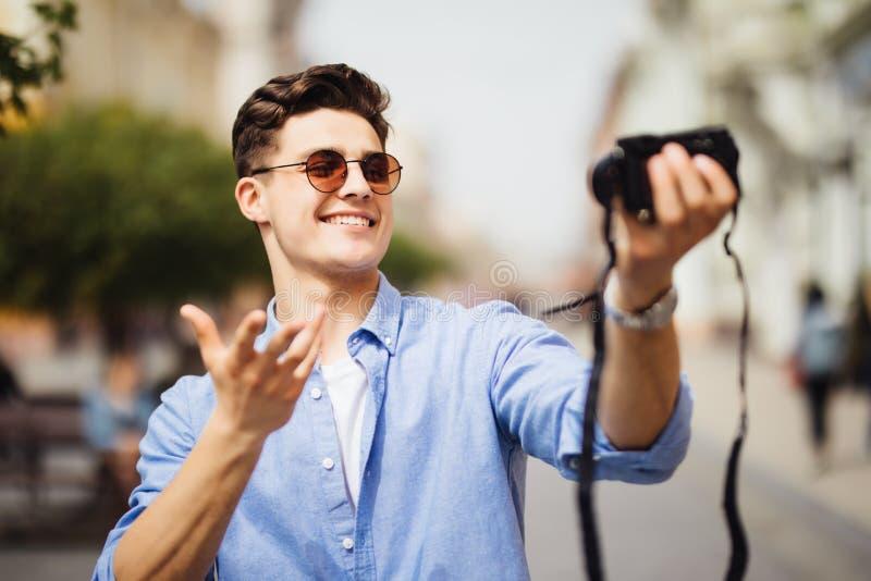 Hübscher Tourist, der ein selfie an der Berufung nimmt Junger Mann, der an der Kamera in einer städtischen Szene lächelt Kaukasis stockfotos