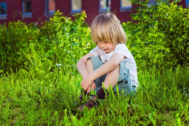 Hübscher trauriger kleiner Junge, der auf Gras sitzt stockbilder