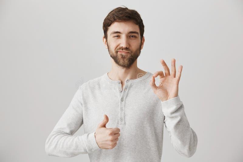 Hübscher und überzeugter europäischer Kerl mit dem Bart, der o.k. oben darstellen oder feine Geste und Daumen, Vergnügen ausdrück stockfotos