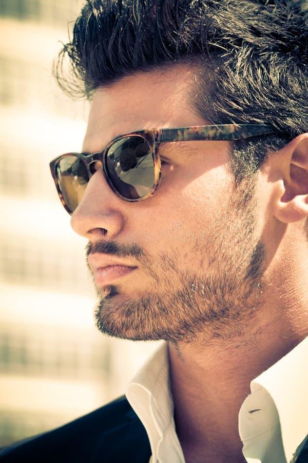 Hübscher und attraktiver junger Mann im Freien mit Sonnenbrille lizenzfreie stockfotos