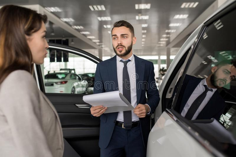 Hübscher Verkäufer Selling Cars im Ausstellungsraum lizenzfreies stockfoto