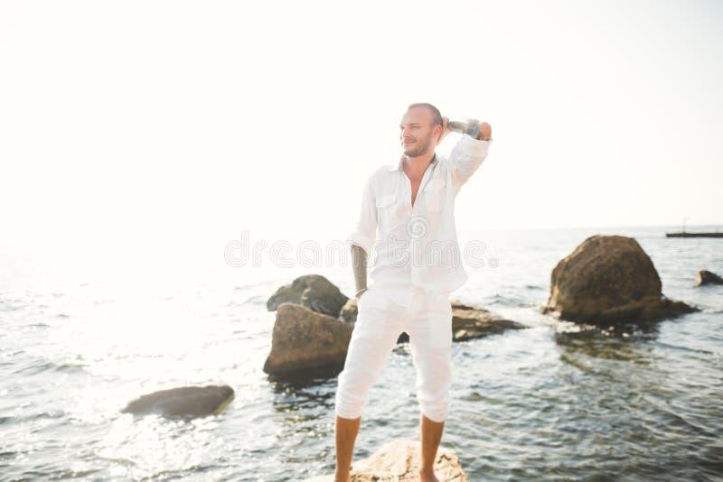 Hübscher vorbildlicher Mann, der auf Stein durch das Meer aufwirft stockbilder