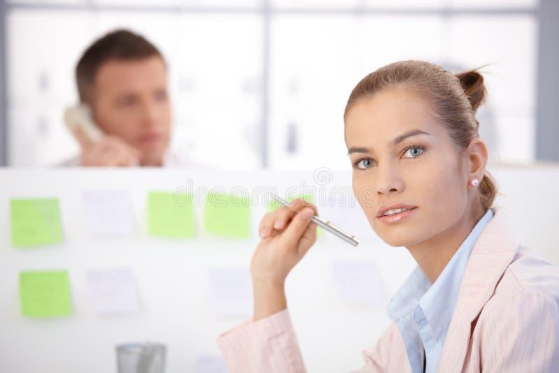 Hübscher weiblicher Büroangestellter, der am Schreibtisch sitzt lizenzfreies stockbild