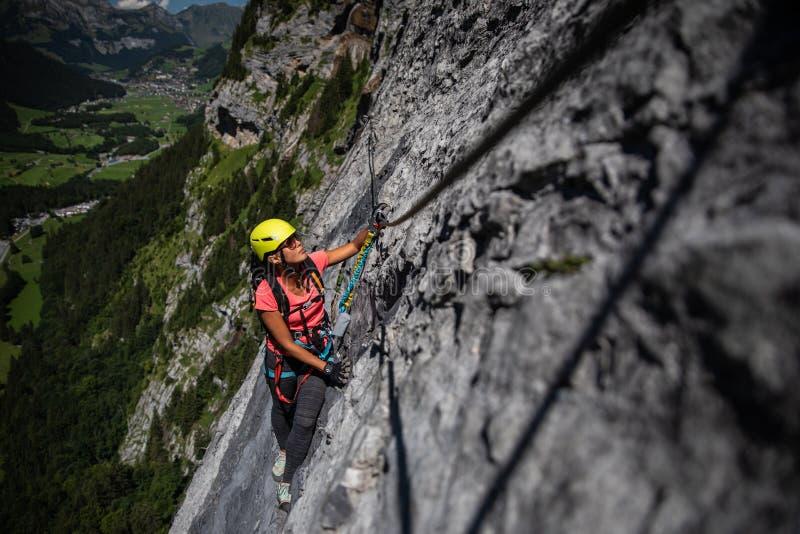 Hübscher, weiblicher Bergsteiger auf a über ferrata stockfotografie