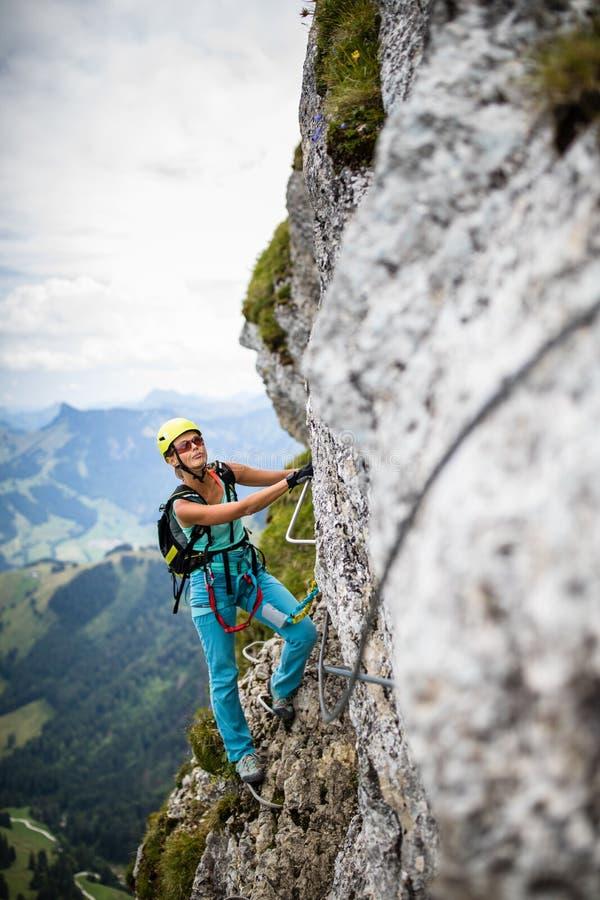 Hübscher, weiblicher Bergsteiger auf a über ferrata stockbilder