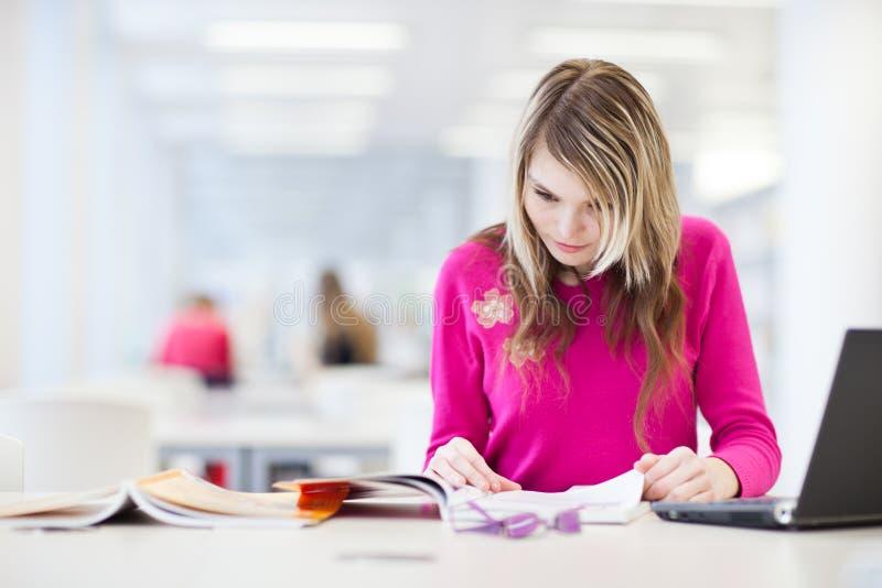 Hübscher, weiblicher Kursteilnehmer mit Laptop und Bücher lizenzfreie stockfotos