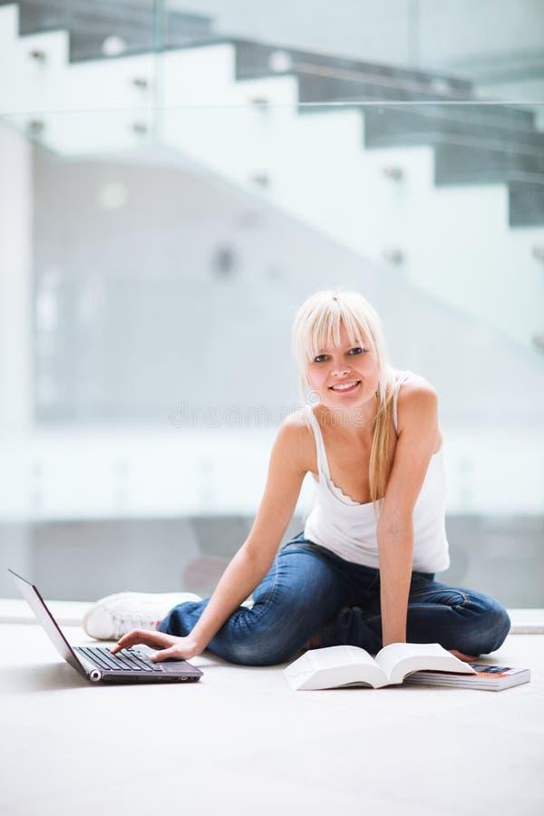 Hübscher weiblicher Kursteilnehmer mit Laptop und Büchern stockbild