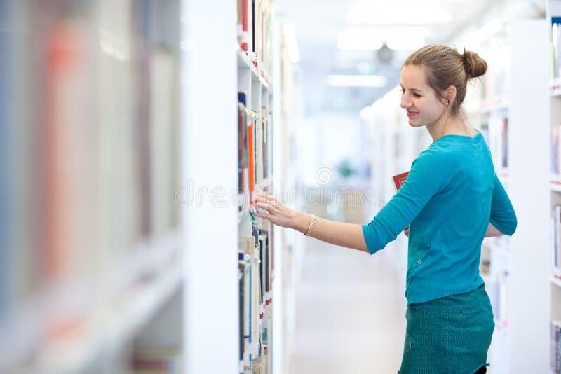 Hübscher weiblicher Student in einer Bibliothek stockbild