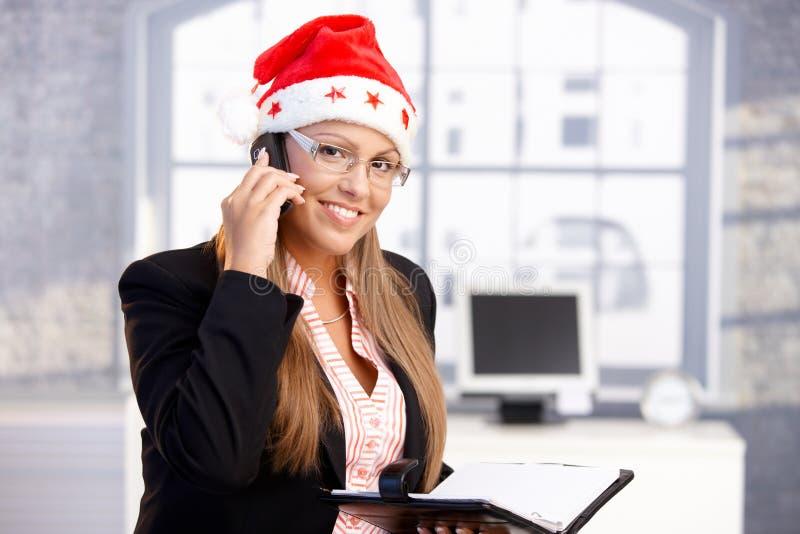 Hübscher weiblicher tragender Sankt-Hut, der im Büro lächelt lizenzfreies stockbild