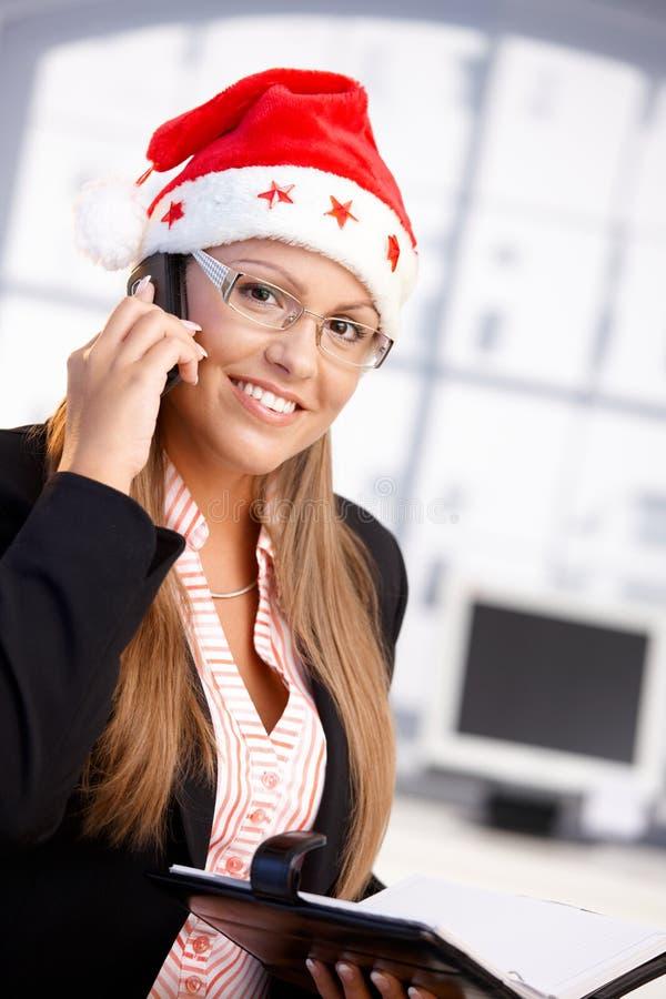 Hübscher weiblicher tragender Sankt-Hut, der im Büro lächelt lizenzfreie stockfotos