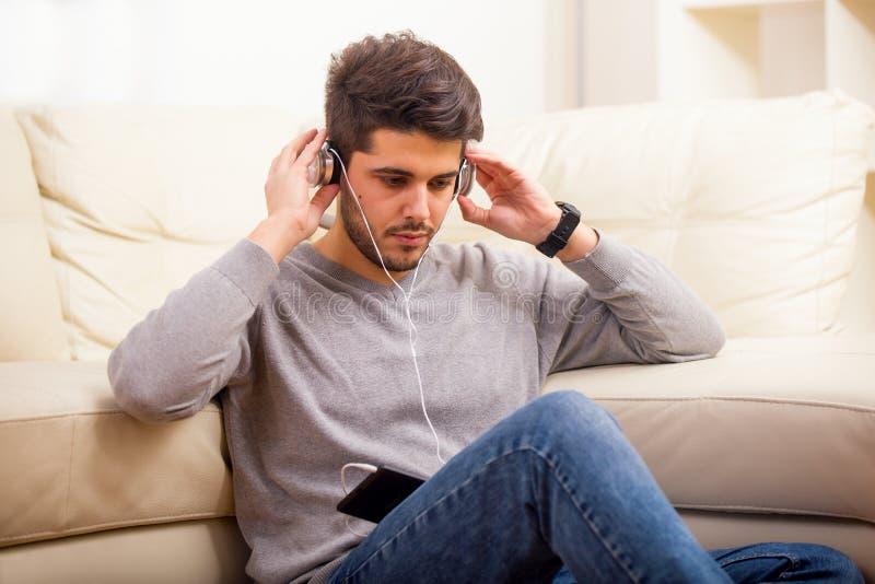 Hübscher zufälliger junger Mann, der zu Hause eine Tablette verwendet stockfoto
