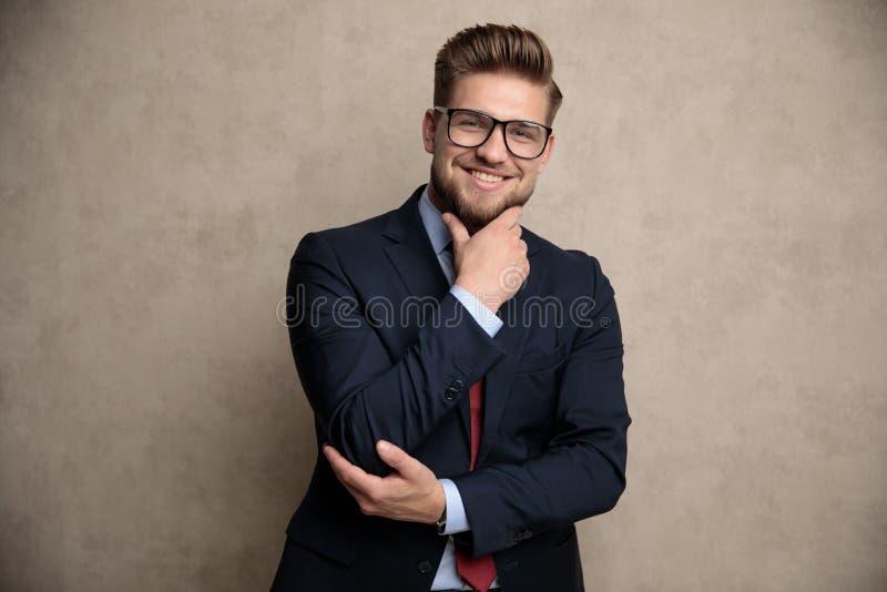 Hübscher zufälliger Mann, der mit seiner Hand auf seinem Kinn aufwirft stockfotos
