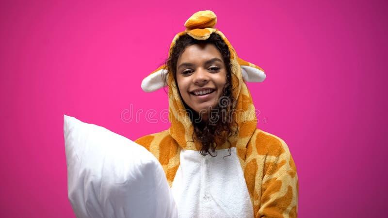 Hübsches afroes-amerikanisch Mädchen im Giraffenpyjama-Holdingkissen, Kamera betrachtend lizenzfreies stockbild