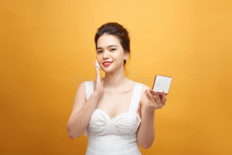 Hübsches asiatisches Mädchenbilden oder -make-up ihr Gesicht durch Hauch das Grundlagenpulver beim Schauen des Spiegels auf der G lizenzfreie stockfotos