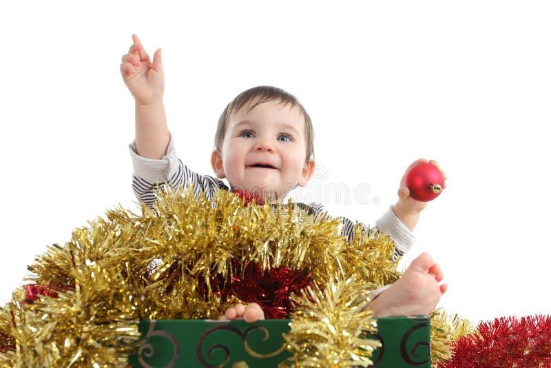 Hübsches Baby innerhalb eines Kastens mit Weihnachtsverzierungen lizenzfreie stockfotos