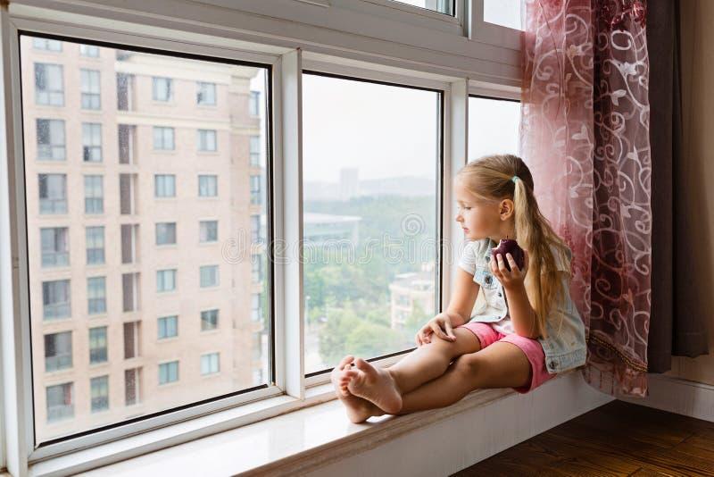 Hübsches blondes kleines Mädchen, das zu Hause auf der Schwelle sitzt, im Fenster schaut und roten Apfel hält Gesundes Nahrungsmi stockfotos