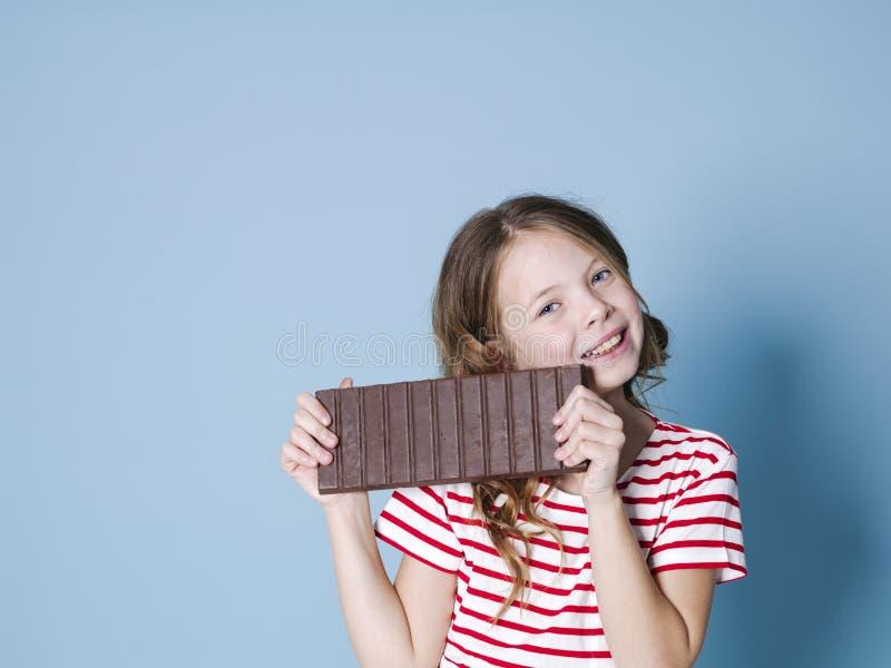 Hübsches blondes Mädchen mit einer riesigen Schokolade wirft vor blauem Hintergrund auf und ist glückliches Lächeln stockfotos