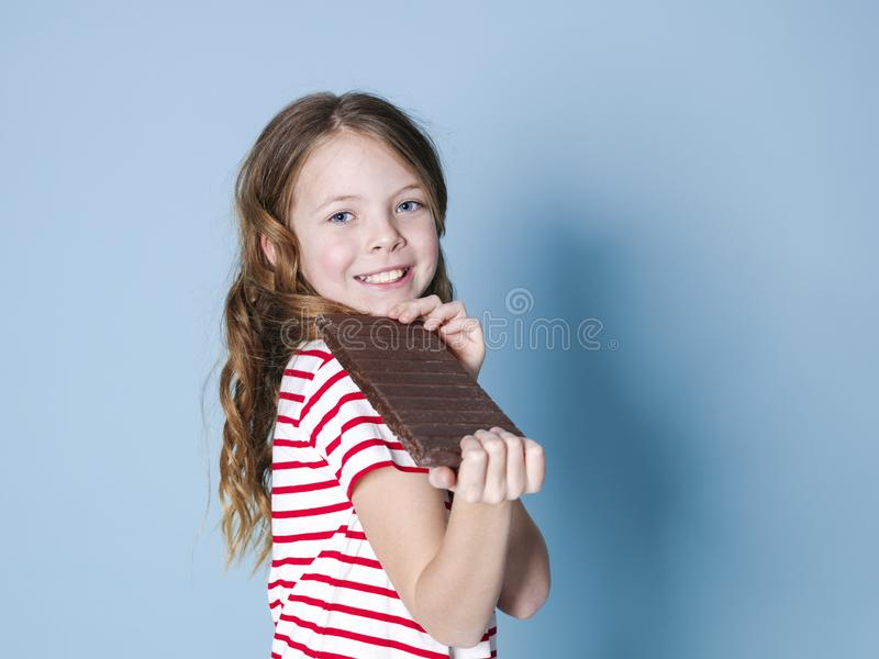 Hübsches blondes Mädchen mit einer riesigen Schokolade wirft vor blauem Hintergrund auf und ist glückliches Lächeln stockbild