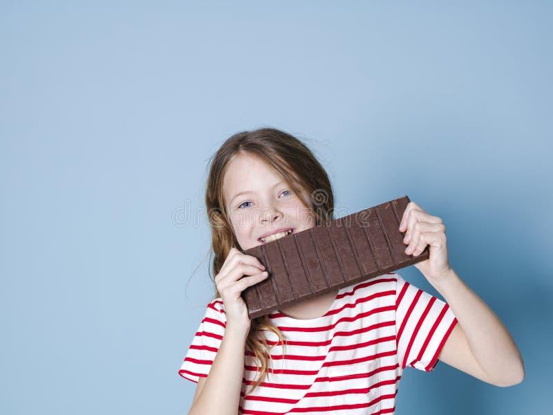 Hübsches blondes Mädchen mit einer riesigen Schokolade wirft vor blauem Hintergrund auf und ist glückliches Lächeln stockbilder