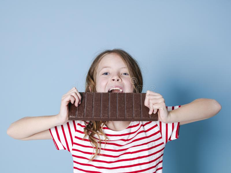 Hübsches blondes Mädchen mit einer riesigen Schokolade wirft vor blauem Hintergrund auf und ist glückliches Lächeln lizenzfreie stockfotos