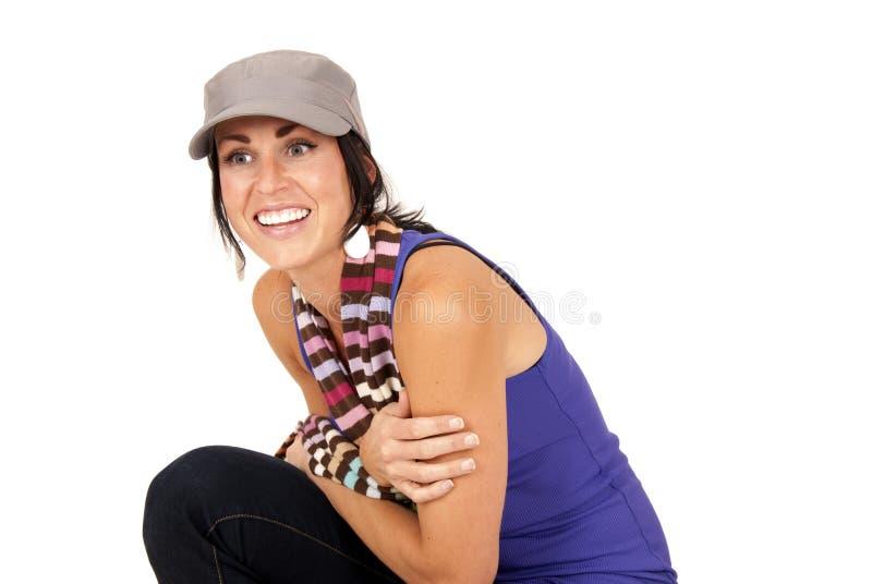 Hübsches Brunettelächeln geduckt unten auf tragendem Schal des Knies und stockfotos