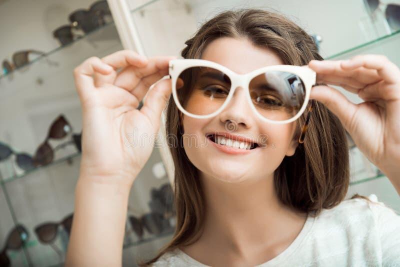 Hübsches Brunettemädchenlächeln, versuchend auf Sonnenbrille im optischen Shop Reizend weibliche Frau beim Sonnenbrillespeichertä stockbilder