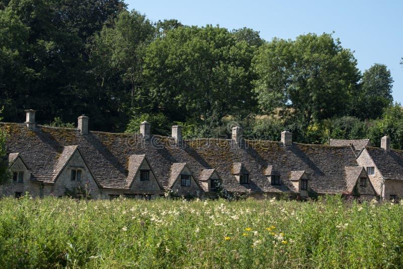 Hübsches Dorf von Bibury im Cotswolds Großbritannien, mit Wasserwiese im Vordergrund und Arlington-Reihenhäuschen an der Rückseit lizenzfreies stockbild