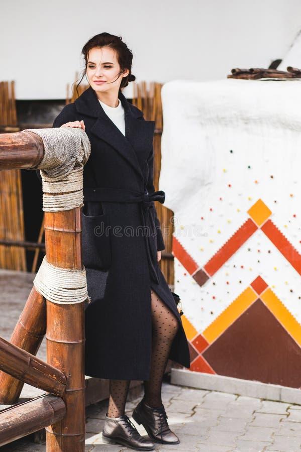 Hübsches Frauenmodell der Mode, das einen dunklen Mantel und eine weiße Strickjacke aufwerfen über ethnischem Hintergrund trägt lizenzfreie stockbilder
