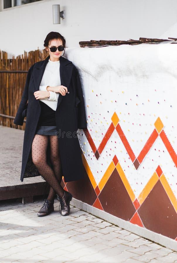 Hübsches Frauenmodell der Mode, das einen dunklen Mantel und eine weiße Strickjacke, in der Sonnenbrille, werfend über weißem Hin stockfoto