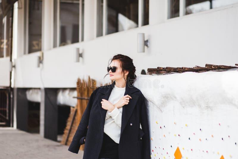 Hübsches Frauenmodell der Mode, das einen dunklen Mantel und eine weiße Strickjacke, in der Sonnenbrille, werfend über weißem Hin lizenzfreies stockbild