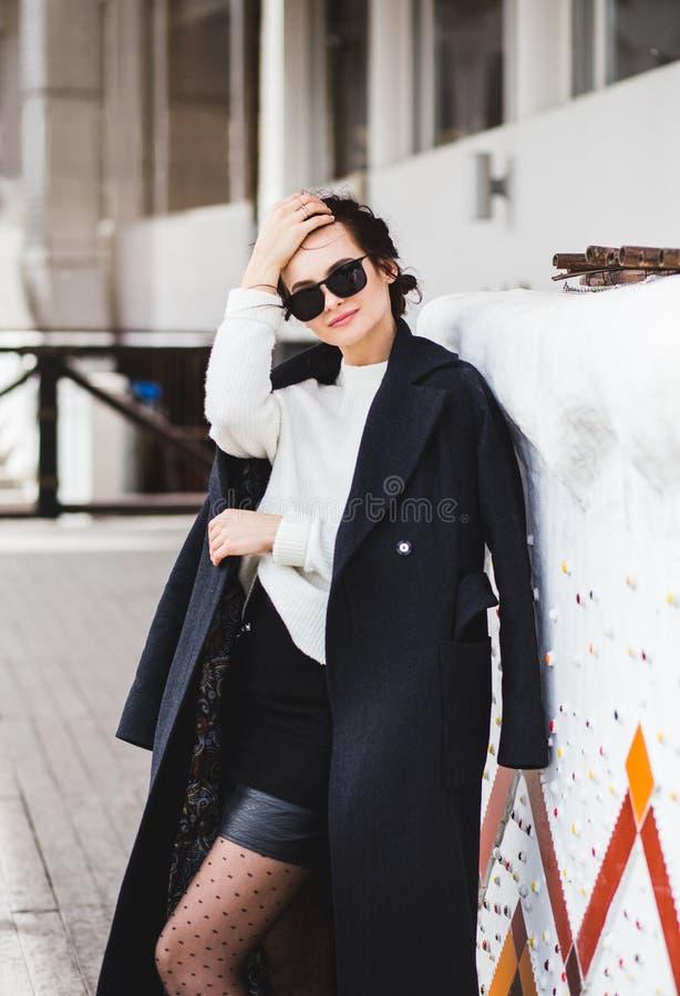 Hübsches Frauenmodell der Mode, das einen dunklen Mantel und eine weiße Strickjacke, in der Sonnenbrille, werfend über weißem Hin stockfotos