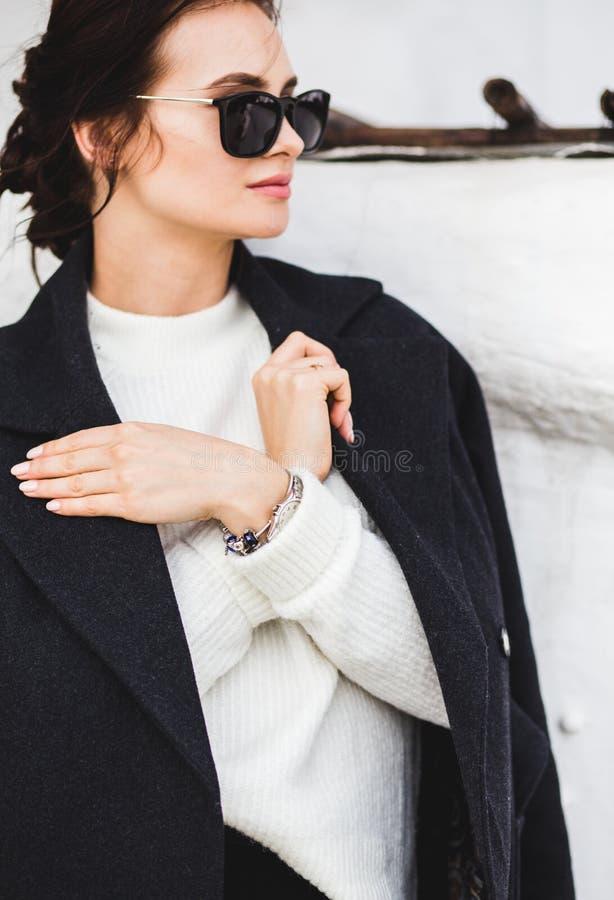 Hübsches Frauenmodell der Mode, das einen dunklen Mantel und eine weiße Strickjacke, in der Sonnenbrille, werfend über weißem Hin stockfotografie