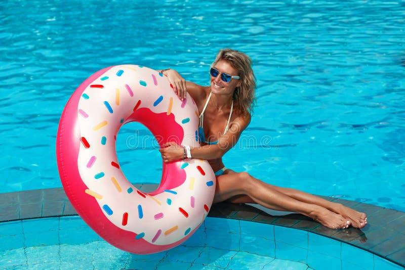 Hübsches Frauenschwimmen auf einem aufblasbaren Kreis stockbilder