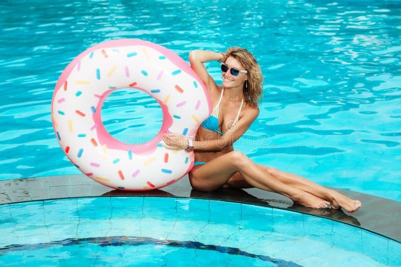 Hübsches Frauenschwimmen auf einem aufblasbaren Kreis stockfotos