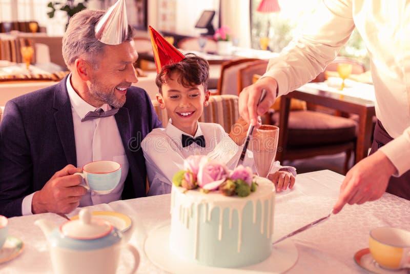 Hübsches Geburtstagsjungengefühl aufgeregt, bevor Kuchen versucht wird lizenzfreies stockfoto