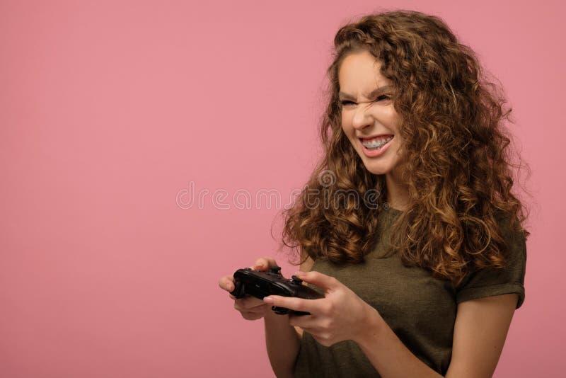 Hübsches Geekenmädchen mit Gamepad auf rosa Untergrund lizenzfreies stockbild