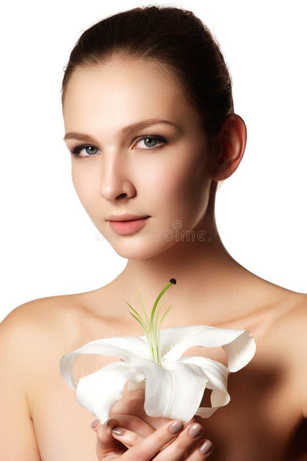 Hübsches Gesicht der schönen jungen Frau mit Lilie auf Händen - Weiß lizenzfreies stockbild