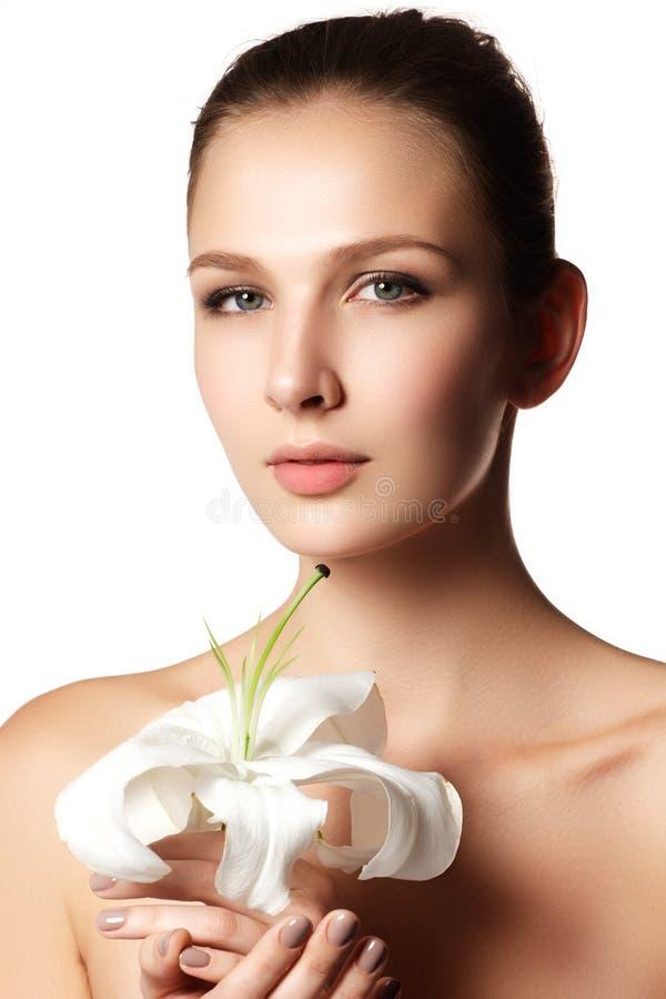 Hübsches Gesicht der schönen jungen Frau mit Lilie auf Händen - Weiß stockfoto